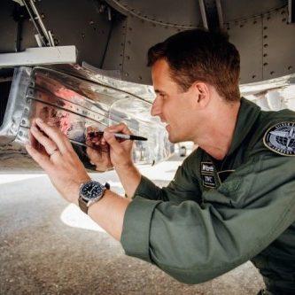 Der CEO der IWC, Christoph Grainger-Herr signiert in Goodwood die Silver Spitfire.