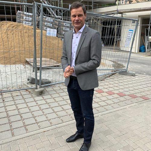 Geschäftsführer Thilo Mühle begrüßt die Gruppe vor der Baustelle der Firmenerweiterung.
