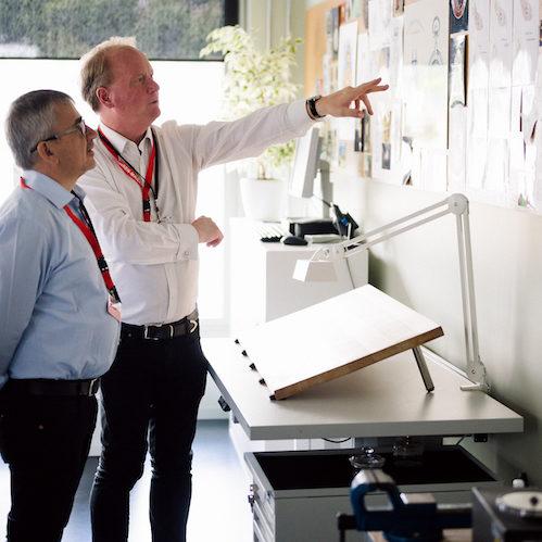 Uhrenexperte und Reiseleiter Tom Wanka mit Leser vor den Entwürfen der Gravuren.