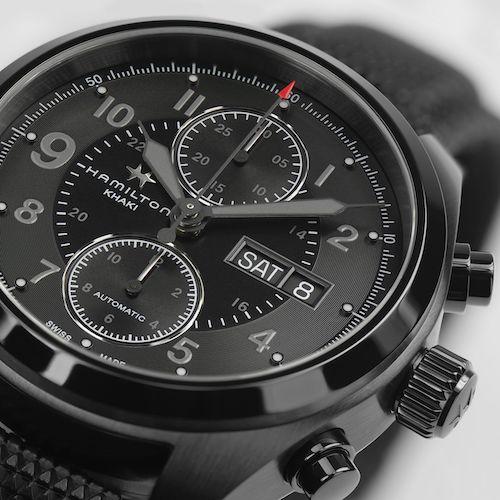 Über dem schwarzen Zifferblatt kreisen Stunden- und Minutenzeiger mit grauer Leuchtfarbe.