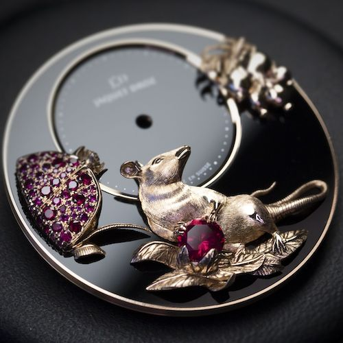 Die Ratte hält einen Granatapfel in den Pfoten, ein Symbol für Fruchtbarkeit.